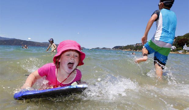 Olivia Weir, 4, mucks around on her surfboard at Scorching Bay, Wellington. Cousin Lucy Stevens, 7, had taught her to surf.