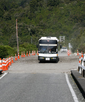 Trapped tourists Phil and June Pharo drive their bus on to the reconstructed Wanganui River bridge as soon as it reopened Monday evening.