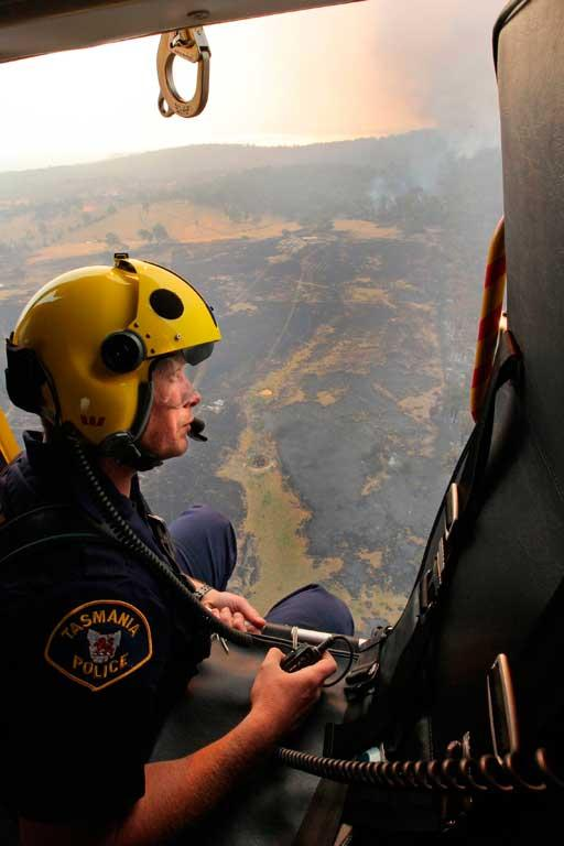 Police Rescue Helicopter crewman Matthew Drumm looks out at the destruction.