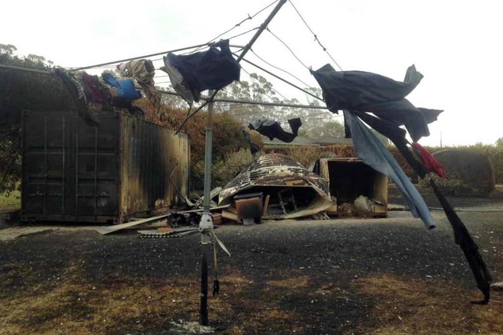 Singed clothes hang from a clothesline in a backyard affected by a bushfire at Boomer Bay, about 40 kilometres east of Hobart.
