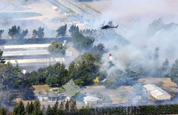 HOMES THREATENED: A helicopter fights fire on Shands Rd.