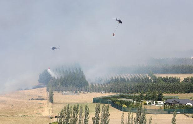 TEAM EFFORT: Two helicopters fight the Shands Rd fire.