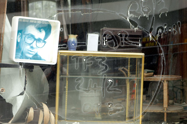Elvis Costello peers out of a deserted shop in Hereford St wearing a faded search and rescue tag.