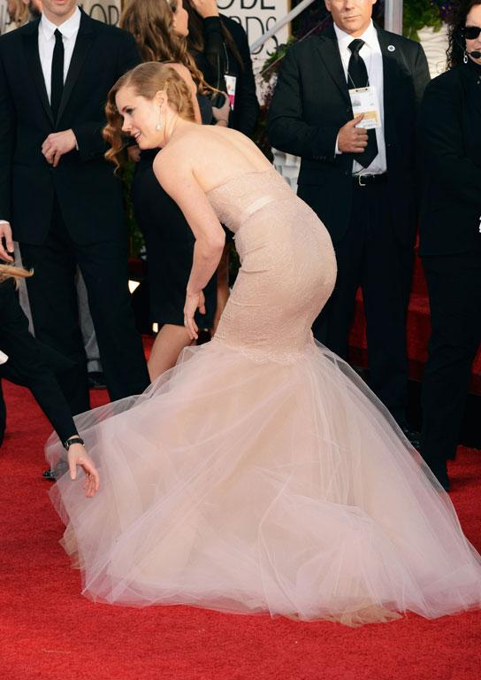 Actress Amy Adams takes a small tumble on the red carpet. Granted, it looks gorgeous, but that blush (or cappuccino?) Marchesa gown must be mighty hard to walk in (let alone sit in during the three hour ceremony).