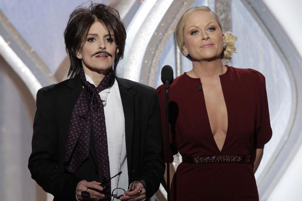 Hosts Tina Fey (as Johnny Depp) and Amy Poehler onstage.