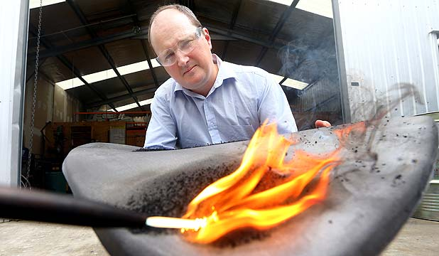 SLOW BURN: Acma director John Bowmar tests the flame resistance of the company's foam train seats.