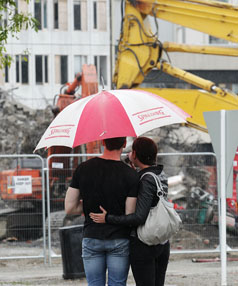 RELIEF: Hedley Roth and Stephanie Kerr cuddle under their umbrella in the Re:Start Mall this morning.