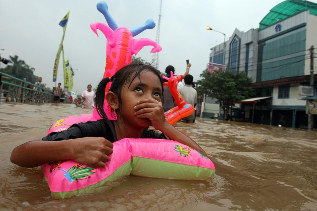 A girl uses a swim ring to wade through a flooded street in Jakarta.