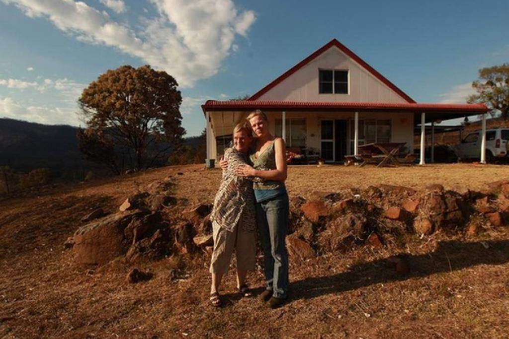 Robina and Felicity Otrupcek standing in front of Robina's home that was water-bombed and remained unscathed as fire burnt through the New South Wales property.