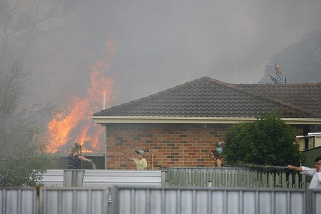 Frantic efforts to damp down properties as the fire approaches.