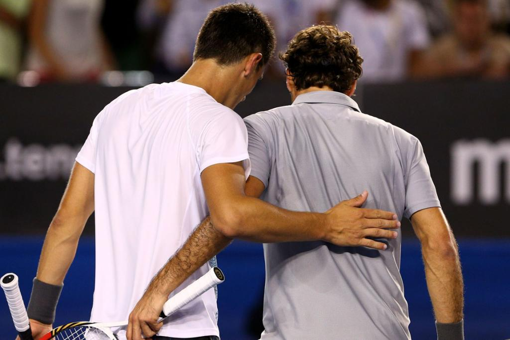 Bernard Tomic and Roger Federer share a pat on the back after their third round match.