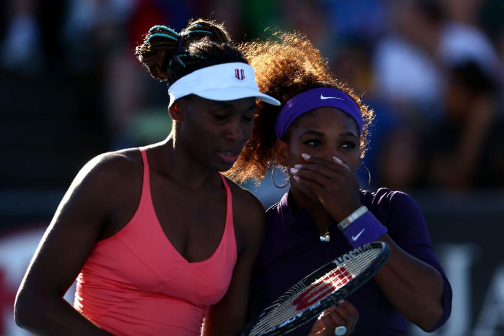 Serena and Venus Williams whisper tactics during their second round doubles match.