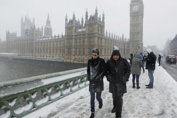 People trudge in the the snow to cross Westminster bridge over the Thames River, past the Houses of Parliament, in central London.