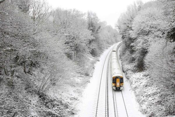 A train travels through countryside covered in snow at Crowhurst near Hastings, south east England.