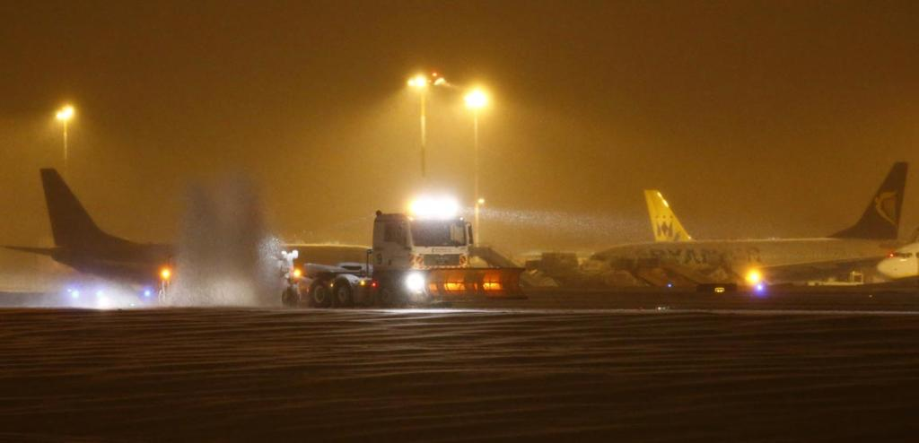 A plough clears snow from the runway at East Midlands Airport near Derby, central England.