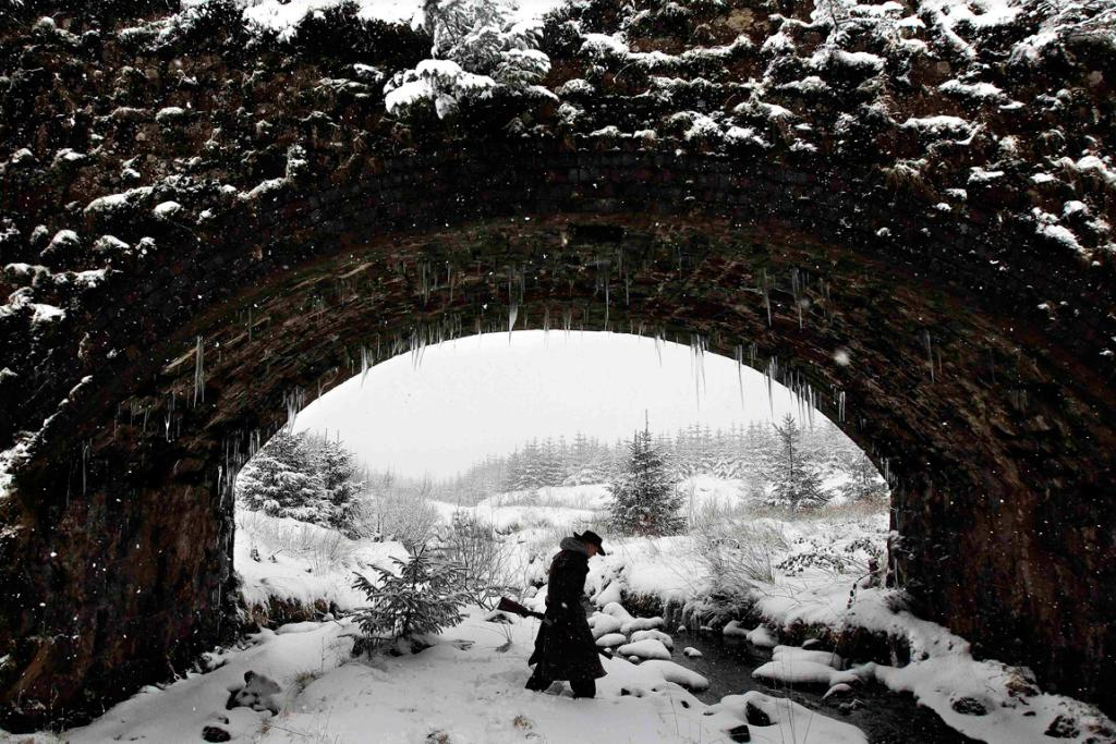 Sheltering under a bridge during a snow storm in the Glens of Antrim near Cargan, Northern Ireland.