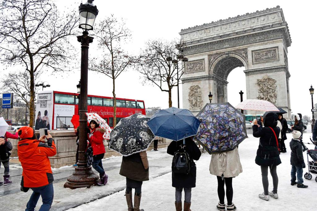 Tourists take pictures in front of the Arc de Triomphe on the Champs Elysees avenue in Paris.