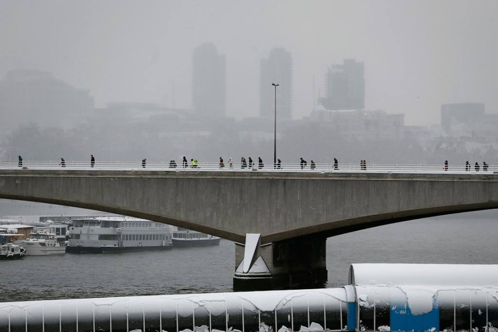 Commuters refuse to let the snow stop them on Waterloo Bridge in central London.