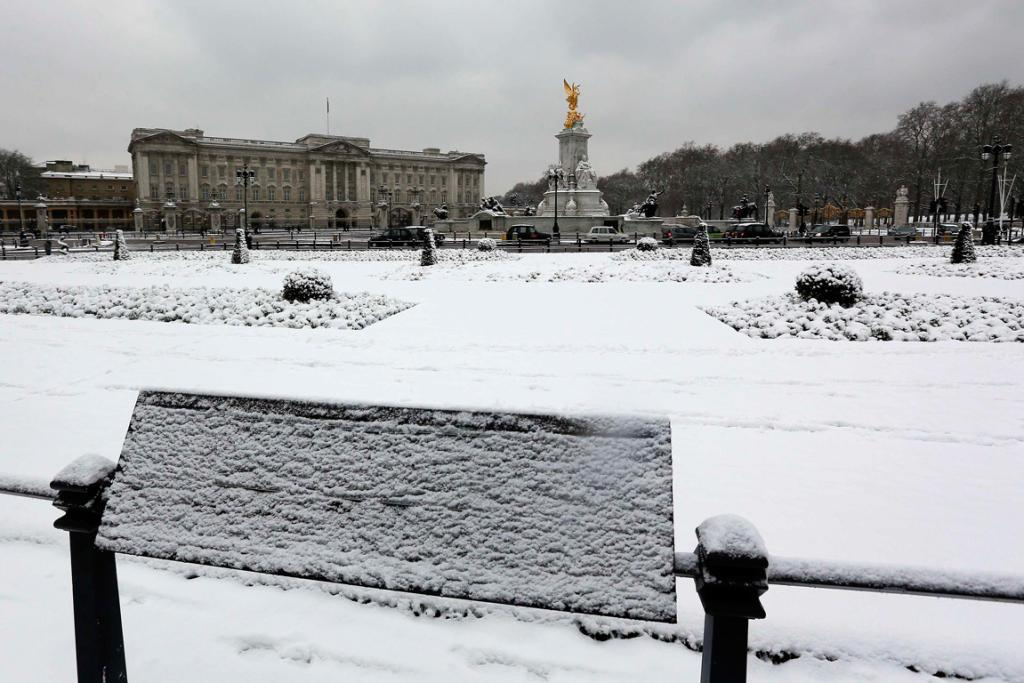 Snow covers the ground in front of Buckingham Palace.