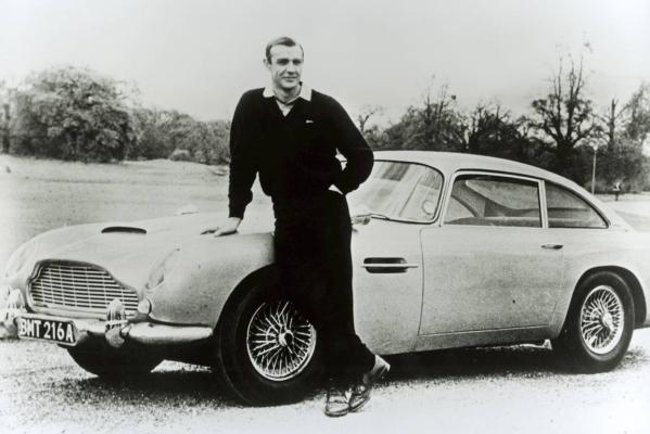 Actor Sean Connery poses on an Aston Martin DB5 during the filming of the James Bond caper Goldfinger in 1964.