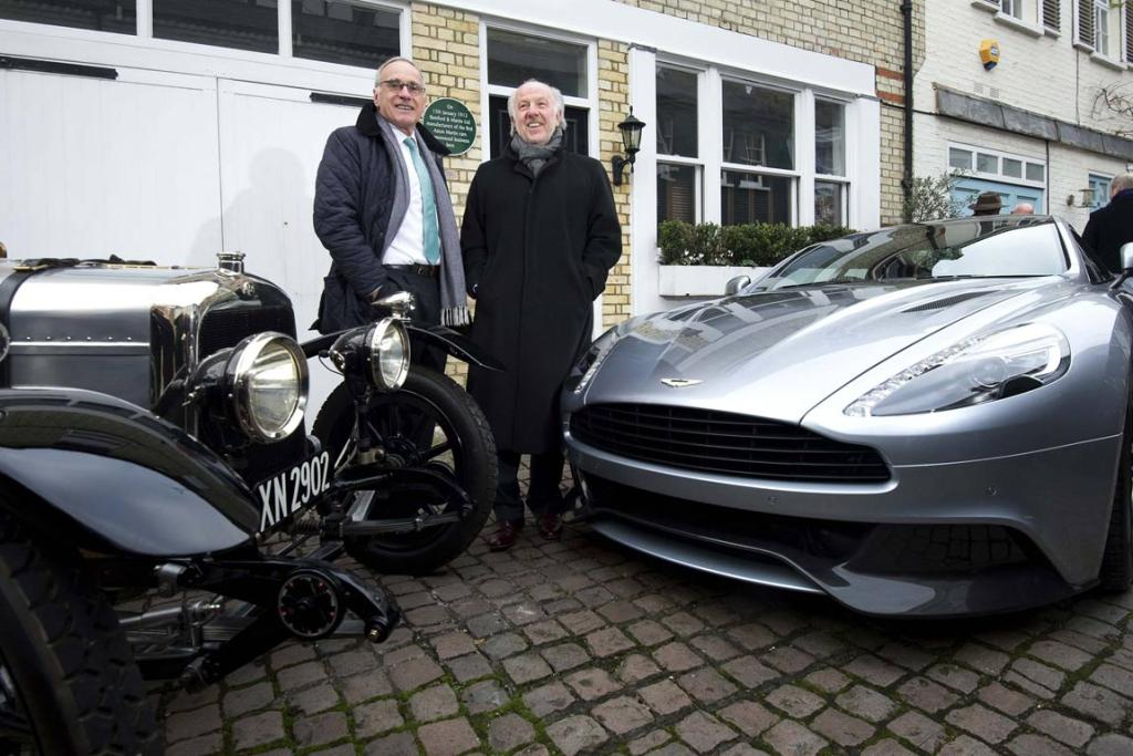 Aston Martin chief executive Ulrich Bez (left) and chairman David Richards pose for photographs next to a 1921 model A3 Aston Martin and a new Aston Martin Vanquish Centenary edition after unveiling a plaque to mark the original place where Aston Martin cars were first manufactured in London January 15, 2013.