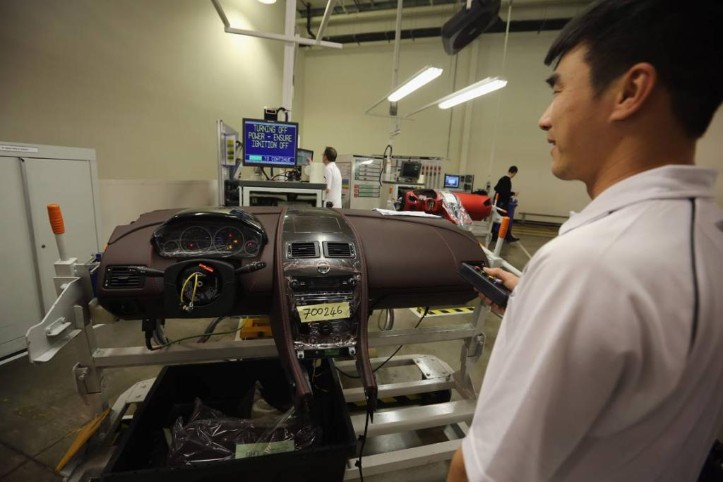 A technician tests the dash board electronics for an Aston Martin motor car at the company headquarters and production plant on January 10, 2013 in Gaydon, England.