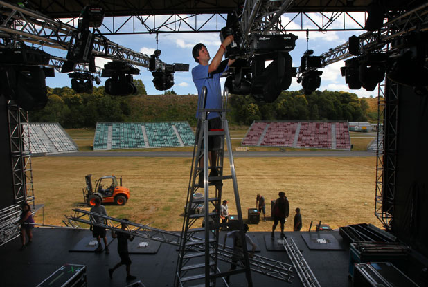 Getting ready: Gerald Hagen, the lighting crew chief at the Parachute Christian music festival, adjusts a light on main stage.
