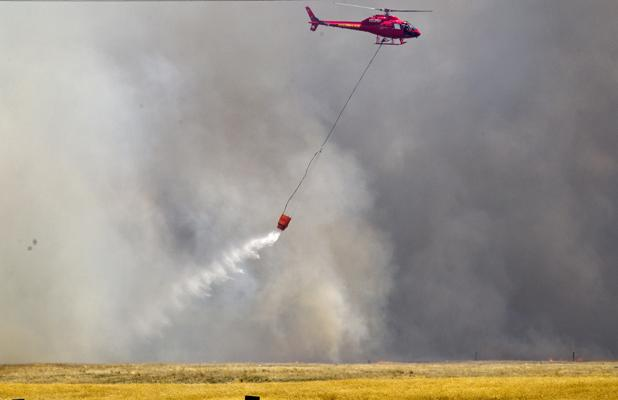 MONSOON: Crews fight a wildfire in paddocks near Weedons Ross Rd and Old West Coast Rd.