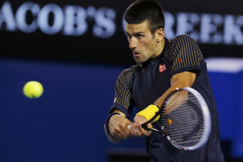 Novak Djokovic of Serbia hits a return to David Ferrer of Spain.