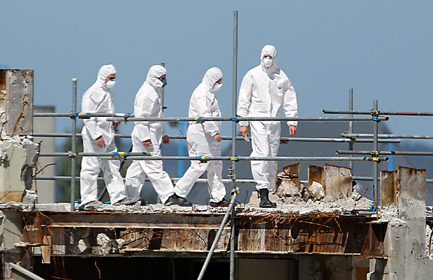 INSPECTION: Workers in protective clothing examine BNZ House, where demolition has been halted.