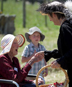 Bessie Berridge shakes hands with Lorraine Agate, who is wearing a black dress worn by Kitty Berridge more than 100 years ago.