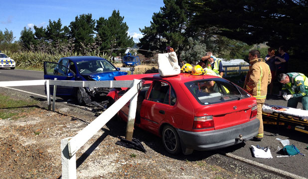 TWO INJURED: Emergency services attend a head-on collision between two cars south of Otaki at the weekend.