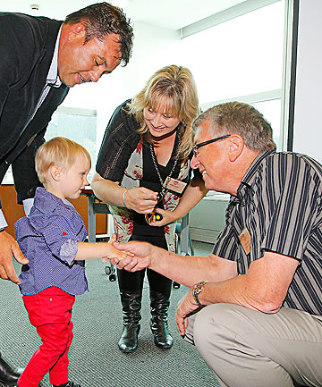 GREAT SAVE: Dennis Roderick shakes hands with Liam Adamson, the toddler he saved.  Liam is accompanied by his mother, Michelle Barr, and father, Jason Adamson. Mr Roderick was yesterday awarded the supreme Highway Heroes award for his efforts.