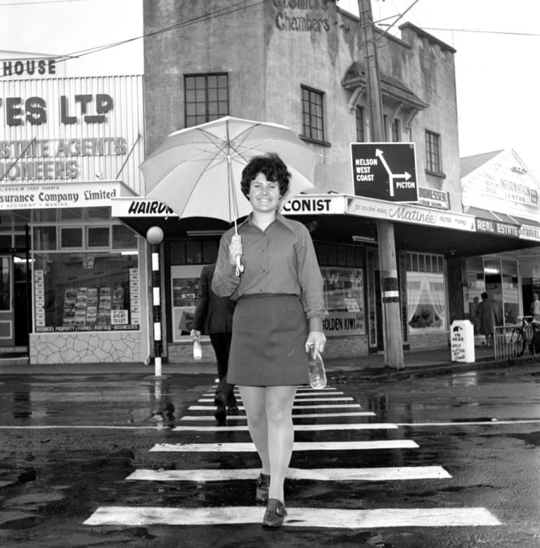 (B0008) This photo was taken in January 1970.  Who is this woman with the empty milk bottle and where was the photo taken? READER UPDATE We understand this is Judith Kirke crossing the High St, Blenheim at the intersection of Market St.