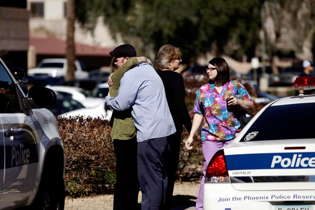 People embrace outside an office building where a gunman fired shots inside in Phoenix.