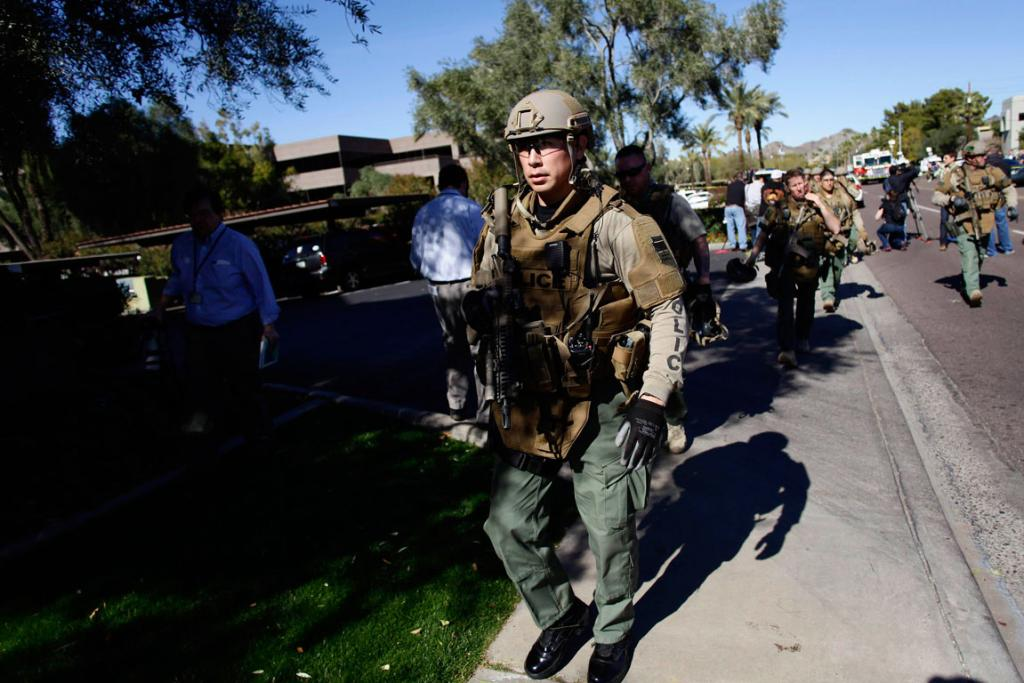 Members of a SWAT team leave the office building.