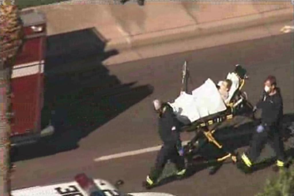 Emergency crews wheel a person on a stretcher from the scene of the shooting.