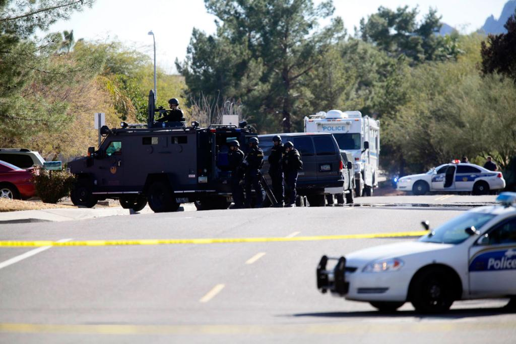 A SWAT team stands surrounds the home of a suspected gunman who fired shots inside an office building during business hours in Phoenix, Arizona.