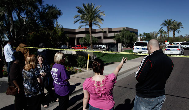 SHOCKED: People gather outside an office building where a gunman shot and wounded several people in Phoenix, Arizona.
