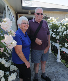 Dawn and Ron Peck are surrounded by the Iceberg roses that edge their front path.