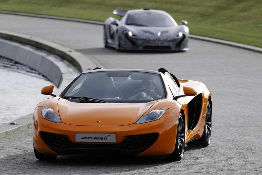 "Sergio ""Checo"" Perez drives the McLaren-heritage orange coloured 12C Spider ahead of Jenson Button in the camouflaged XP prototype version of the McLaren P1 at the company's unveiling of their 2013 Formula One challenger."