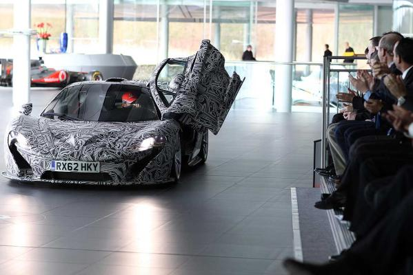 Jenson Button opens the door of the camouflaged XP prototype version of the McLaren P1 in front of invited guests ahead of the company's unveiling of their 2013 Formula One challenger.