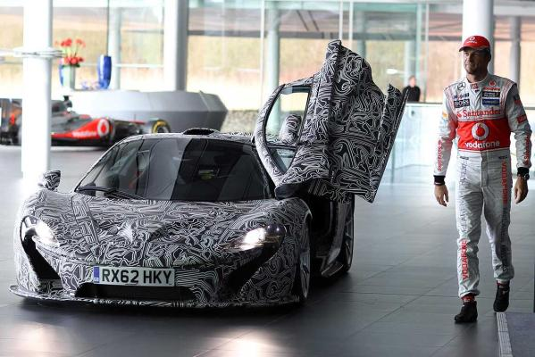 Jenson Button leaves the door of the camouflaged XP prototype version of the McLaren P1 open after arriving for the company's unveiling of their 2013 Formula One challenger.