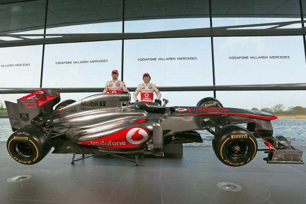McLaren Formula One drivers Jenson Button of Britain (left) and Sergio Perez of Mexico pose for photographers after unveiling the McLaren MP4-28 car at the company's headquarters in Woking, southern England.