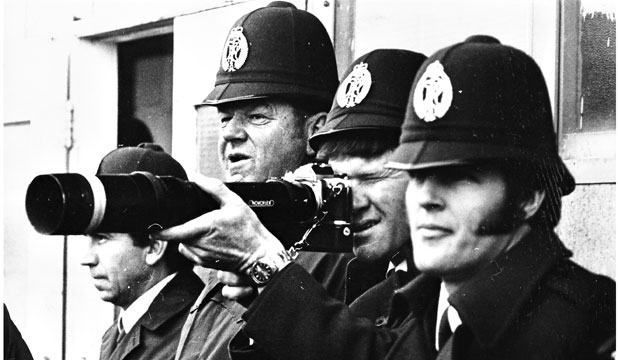 DIFFERING VIEWS: NZ Police officers in 1981 at the Bay of Plenty versus Springboks game at Rotorua borrow a photographer's camera to watch the action up close.