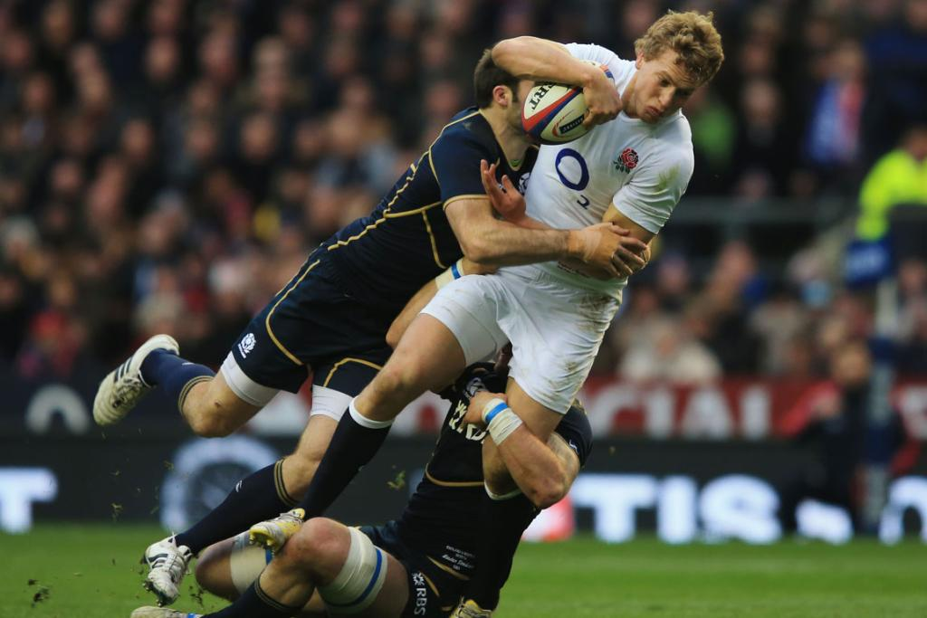Billy Twelvetrees of England is hauled down by the Scotland defence.