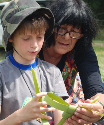 Margaret Bond teaches Owen Sidley, 8, how to weave with harakeke (flax).