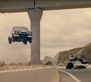 A Mk1 Ford Escort is airborne during a trailer for the latest Fast and Furious movie as a tank is about to crush a Ford Mustang in background.