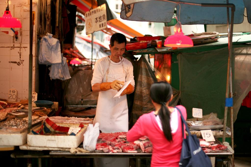 A butcher serves a customer from his street-side shop.