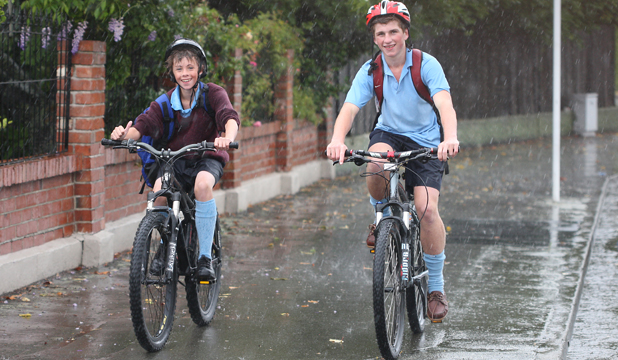 DAMP DAY: Trying to get home in the wet weather after a day at school are Logan Fynn, left, and Chris Hogg.